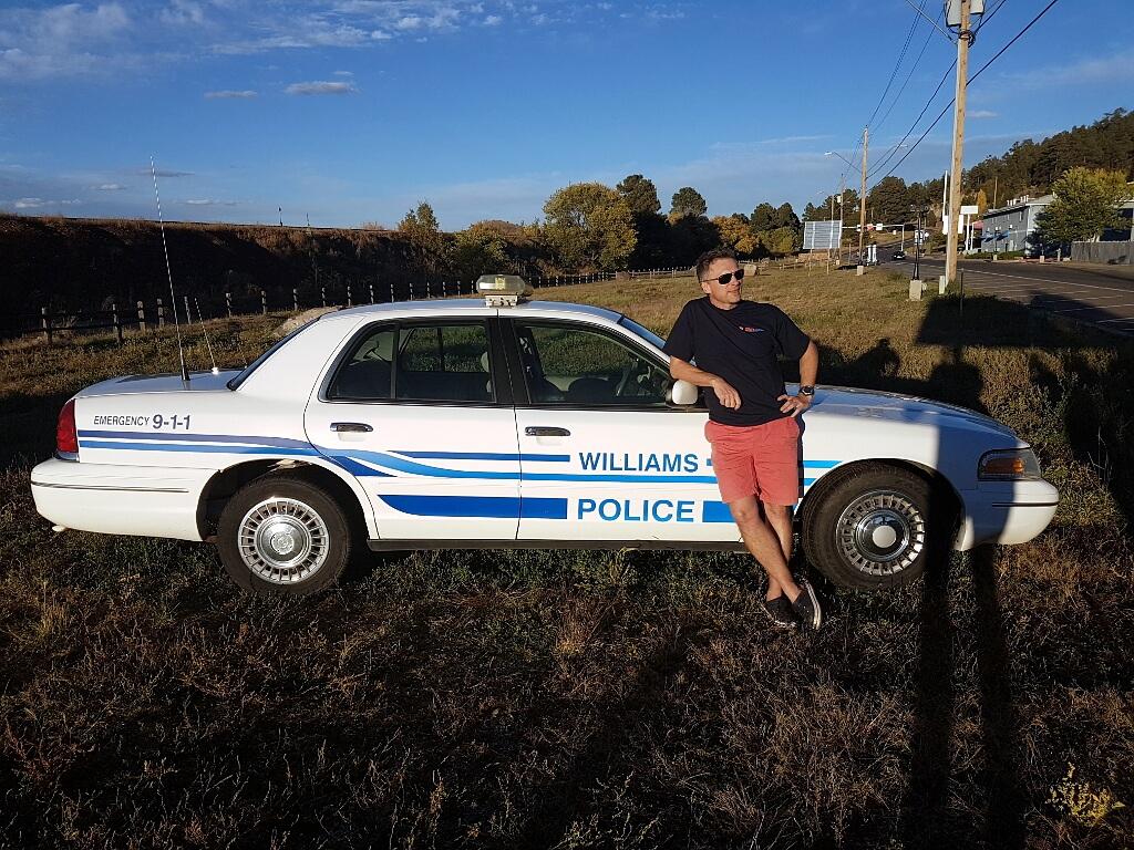 Darek na tle samochodu policyjnego