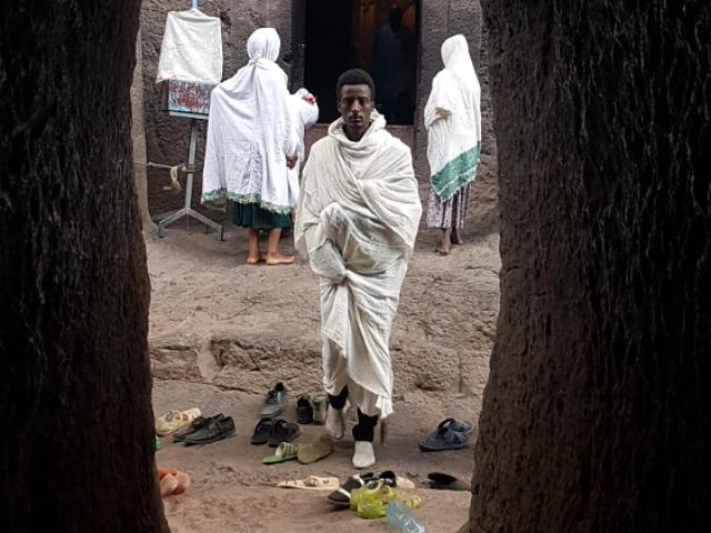 Etiopczyk w białej szacie widziany w skalnym tunelu