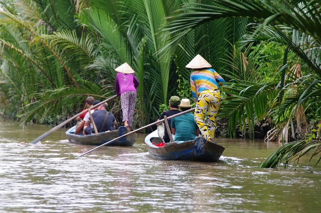 Dwie łodzie prowadzone przez kolorowo ubrane Wietnamki